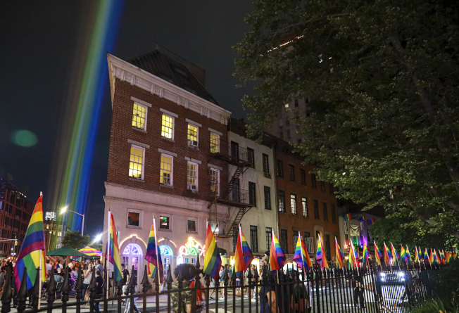紐約西村的石牆酒吧旁,27日晚布置了彩虹旗及投射光。51年前發生在石牆酒吧的暴力事件,成為同志平權運動的重要起點。(美聯社)