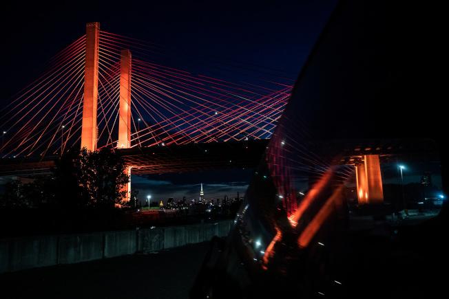 紐約紀念石牆酒吧事件51周年,連接皇后區和布魯克林的 Kosciuszko 大橋,在夜色中散發彩虹光,支持同志運動。(路透)