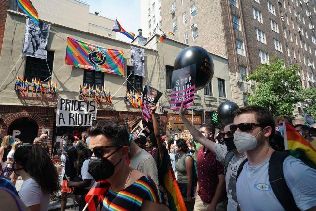 紐約民眾28日紀念石牆事件51周年,遊行經過石牆酒吧門前。(美聯社)