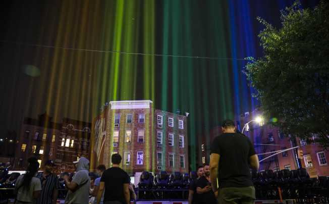 紐約西村靠近石牆酒吧處,27日晚向夜空打出彩虹光芒,紀念「石牆事件」51周年。(美聯社)
