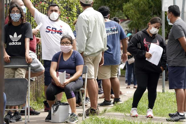 美國新冠疫情持續擴大蔓延,現在美國南部與西部的情況嚴重。許多人趕著做新冠檢測,以致大排長龍。圖為28日在休士頓的墨西哥駐美國總領事館前等候接受檢驗的人龍隊伍。(美聯社)
