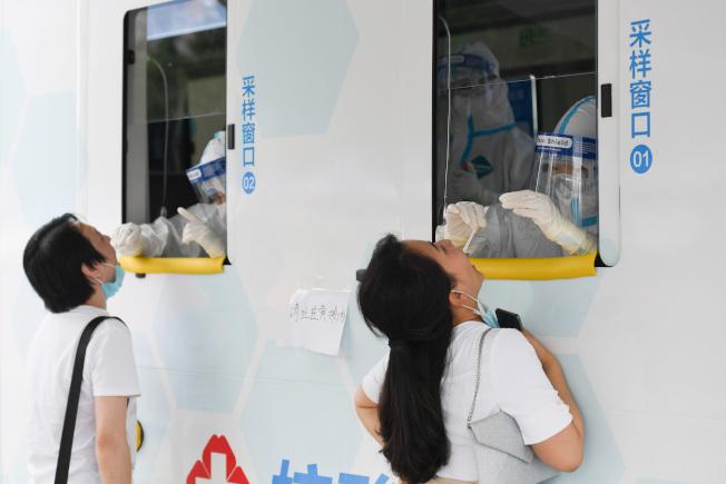 圖為西城區北京展覽館南側的露天廣場核酸檢測採樣點,核酸檢測採樣車內的醫護人員為前來做檢測的人員進行採樣。(新華社)