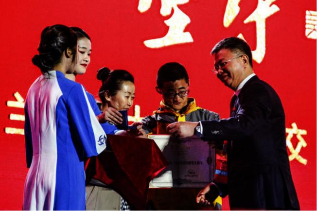 校长严纯华授予谢炎廷「荣誉研究生」称号,并爲他佩戴校徽。(取材自兰州大学新闻网)