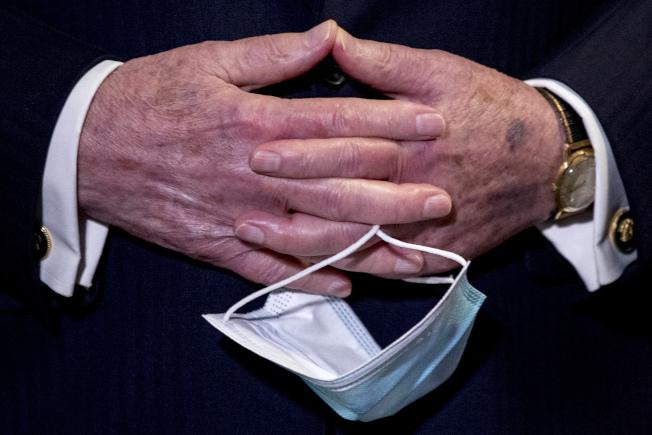 戴不戴口罩?華府政要做法不同。參院多數黨領袖麥康諾上周在會議中,手上拿著口罩。(美聯社)