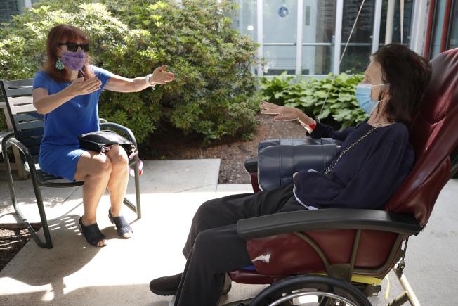 根據統計美國這次新冠疫情,以老人年死亡人數最多,成為新冠高危族群,需要特殊照顧。圖為在波士頓的女兒摩瑞絲(左),遠距離探視在養老院的母親辛西亞。(美聯社)ndola)