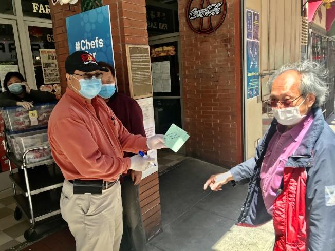 康年海鮮酒家東主李彪(右)和經理鮑志榮(左),向一名出示餐券的「疫境送暖、燃亮華埠」計畫居民(中)送出午餐。(記者黃少華/攝影)