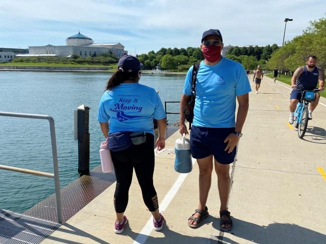 穿著淡藍色印有「keep it moving」字樣T恤的社交距離大使,每天會在密西根湖畔巡邏。(特派員黃惠玲/攝影)