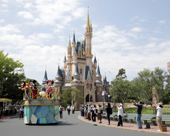 日本東京迪士尼樂園將於7月1日採限制人數方式重新開園,園內的吉祥物也會跟遊客保持距離,配合音樂節奏揮手歡迎遊客入場,但不會跟遊客有所碰觸。(歐新社)