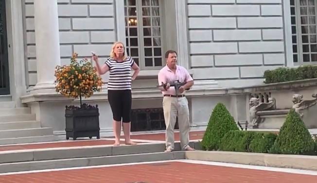 麥考科拉斯夫婦手拿長短槍,指著擅闖私人財產的示威群眾。(推特影片截圖)