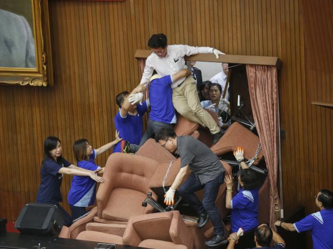 國民黨團28日突襲占據立法院議場,民進黨立委隔天反攻,立委郭國文(上)率先從右邊的後門爬進議場。(記者鄭超文/攝影)