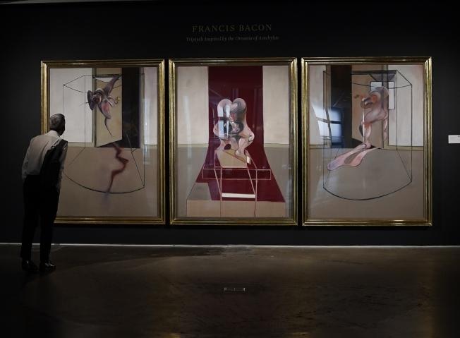 圖為一男子正在觀看英國畫家培根(Francis Bacon)的三聯畫。Getty Images