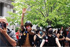 聚集在紐約市警總局門前示威者,向在場的警員豎起中指。(記者張晨/攝影)