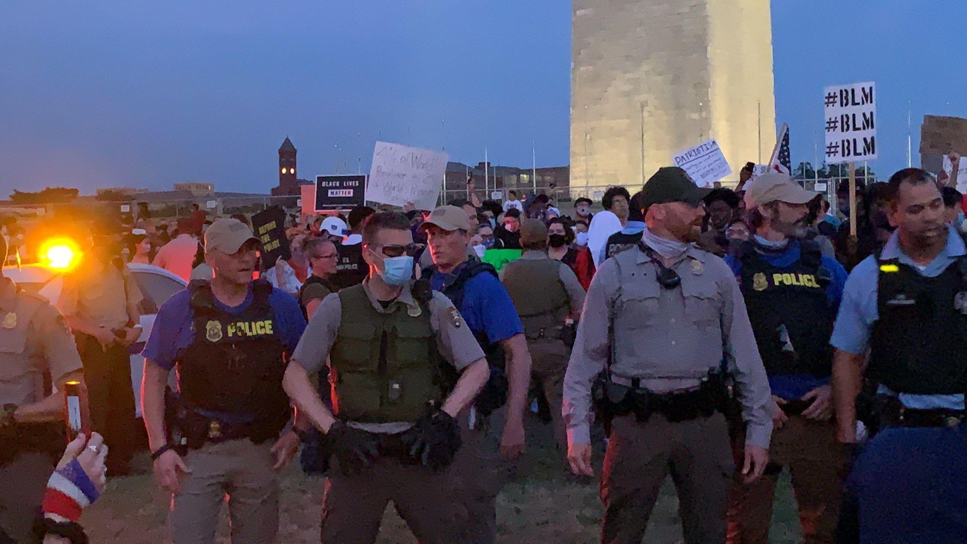 數十名警察在煙火秀開始前迅速包圍示威群眾。(記者張筠 / 攝影)