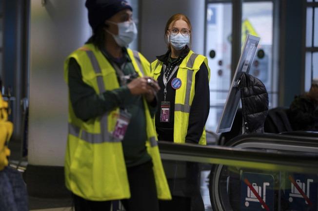 來自2019冠狀病毒疾病(COVID-19)疫情嚴重的15州,進入芝加哥都必須先隔離14天。圖為機場工作人員戴上口罩。美聯社