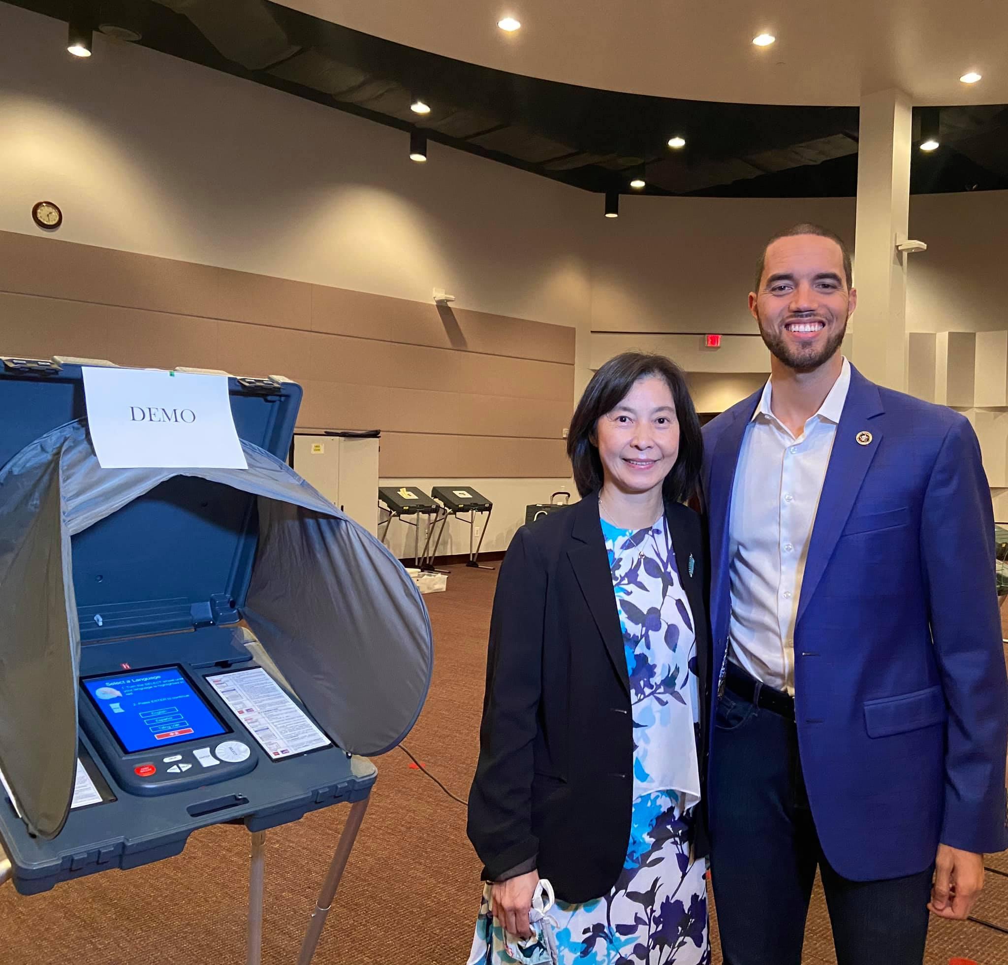 Harris縣行政書記官Chris Hollins (右)與芮久玖(左)介紹投票所為應對疫情,提供選民及選務人員新的安全措施及服務項目。(芮久玟提供)