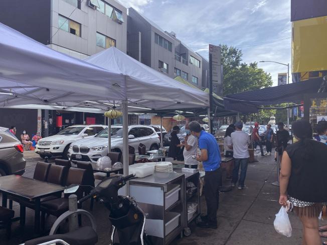 法拉盛有中餐館在門前的馬路上設攤售賣美食,受到民眾歡迎。(記者牟蘭╱攝影)