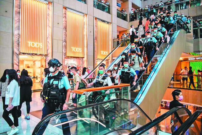 香港警方進入一間商場,驅散午餐時間集結抗議港區國安法的群眾。(Getty Images)