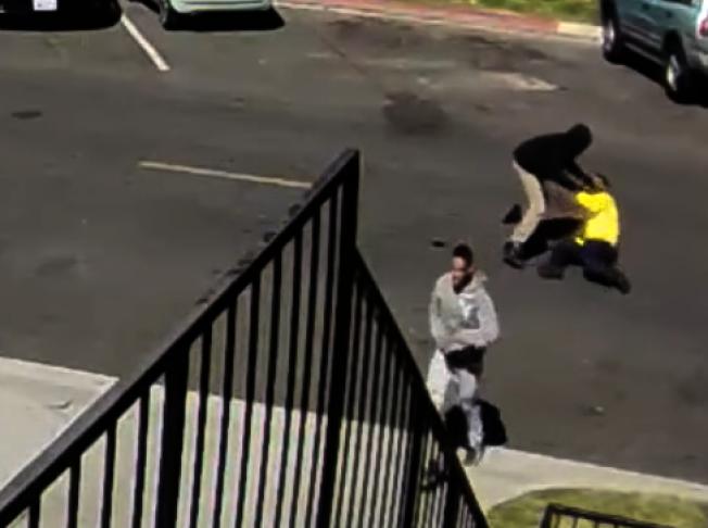 一名嫌犯将受害者打倒在地,另一名嫌犯在望风。 (长堤市警局提供)