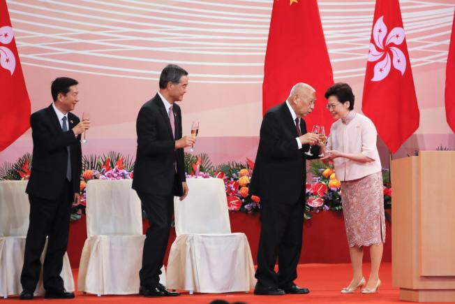 香港政府舉行酒會慶祝成立香港回歸23年23周年。香港特首林鄭月娥(右)與前特首董建華(右二)互相敬酒,另一位前特首梁振英(左二)在旁邊等候。(美聯社)