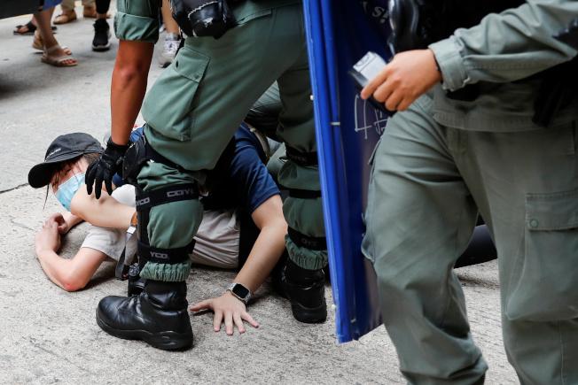 中國「港區國安法」上路首日,數萬香港民眾上街示威。圖為一名示威者被港警壓壓制在地。(路透)