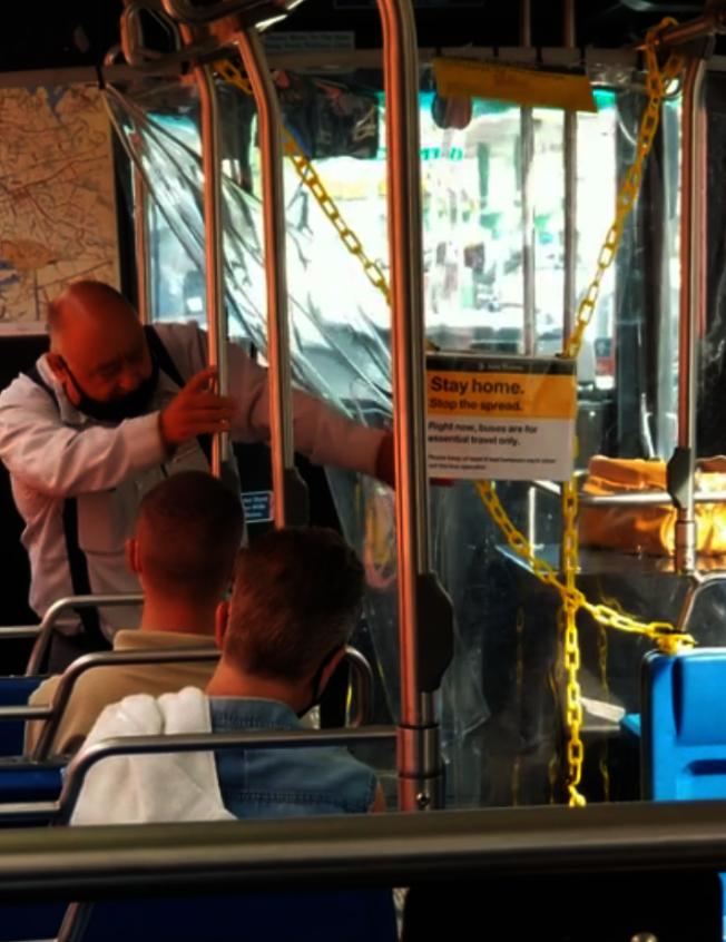 男乘客穿過保護公車司機的塑料屏障,回到乘客區。(reddit網站上的視頻截圖)