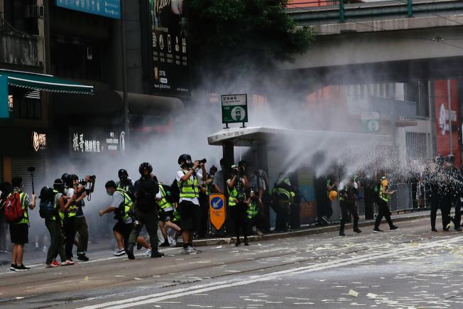 警查用水炮車驅散在場群眾,有記者因此受傷。(路透)
