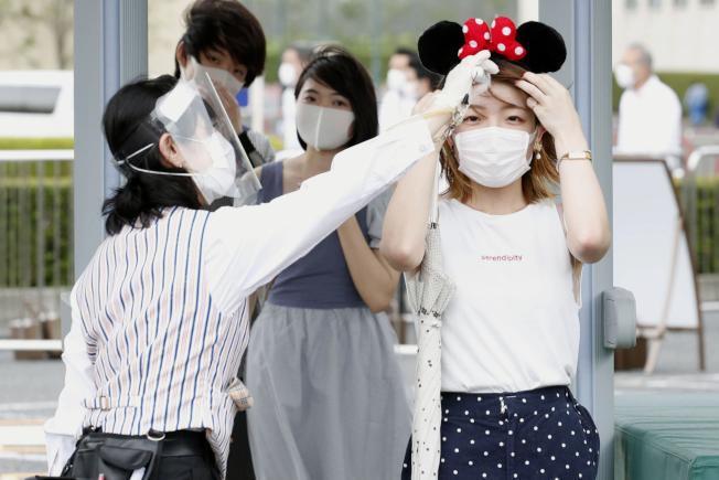 日本內閣官房長官菅義偉1日說,未來確診病例急速增加的話,最糟的情況有可能再度公布「緊急事態宣言」。圖為東京迪士尼因疫情關閉四個月後,重新開啟。(美聯社)