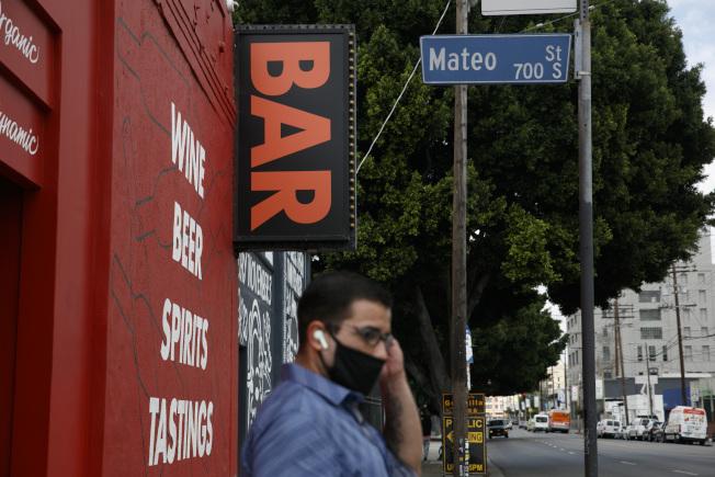 加州1日新冠肺炎新增確診近5900例和死亡逾110例,過去兩周確診增加近50%,住院率也成長43%;州長紐森宣布關閉洛杉磯等19郡的酒吧和餐廳堂食。圖為洛杉磯一家關閉的酒吧前,一男子正在公車。(美聯社)