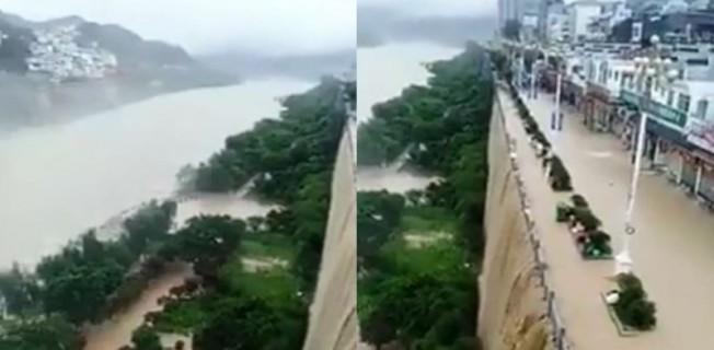 重慶市近來不斷面臨暴雨成災,當地河濱商店街被積水淹沒,黃泥水從峭壁傾瀉而下簡直成了瀑布。(取材自微博)