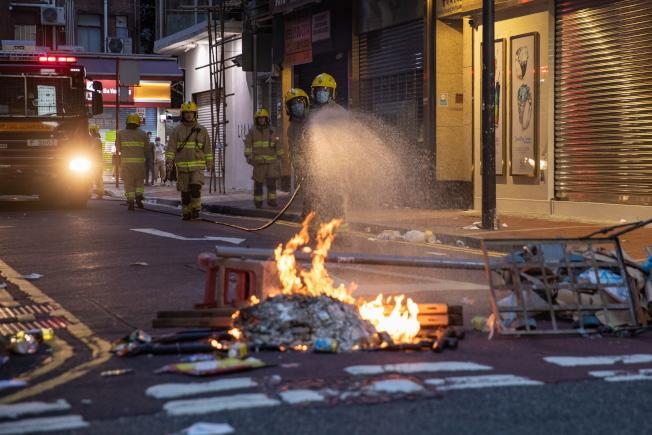 「港區國安法」上路,香港街頭出現示威人潮,一名消防員為著火的路障。(Getty Images)