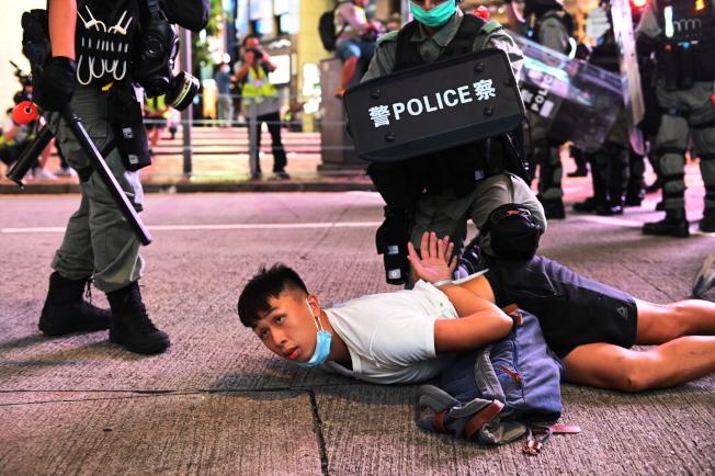 「港區國安法」上路,香港街頭出現示威人潮,一名示威者被港警壓制在地面。(歐新社)