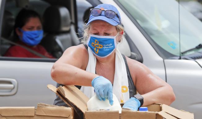 德州疫情升高,州長艾伯特宣布周五起要戴口罩。圖為德州達拉斯一名志願者戴著口罩分發食物。(美聯社)