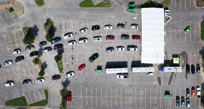 德州疫情升高,州長艾伯特宣布周五起要戴口罩。圖為德州達拉斯民眾開車等待做病毒檢測。(Getty Images)