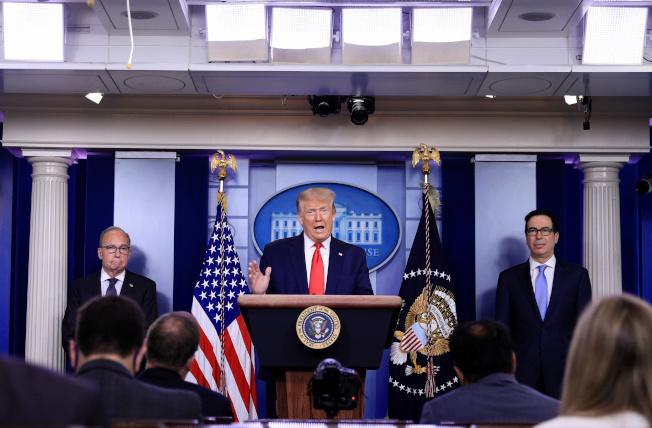 川普總統(中)2日在白宮的記者會上表示,美國經濟依然強勁。圖左為白宮經濟顧問庫德洛,右為財長米努勤。(路透)