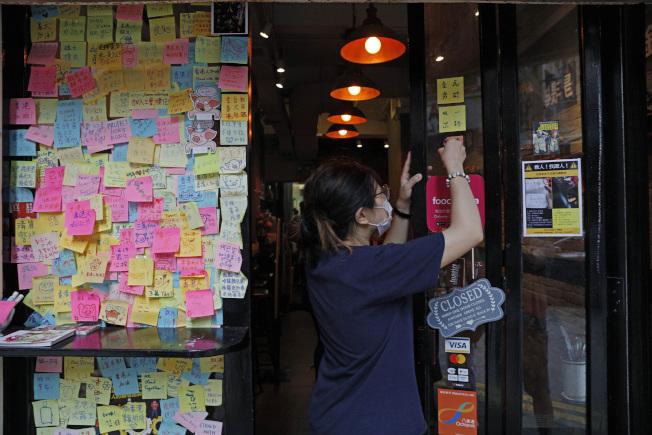 北京當局趁分裂的西方國家無能力因應之機,收緊對香港的控制,民眾只好自求多福。圖為2日一餐館服務生鏟除牆上支持香港民主運動的標語。 (美聯社)