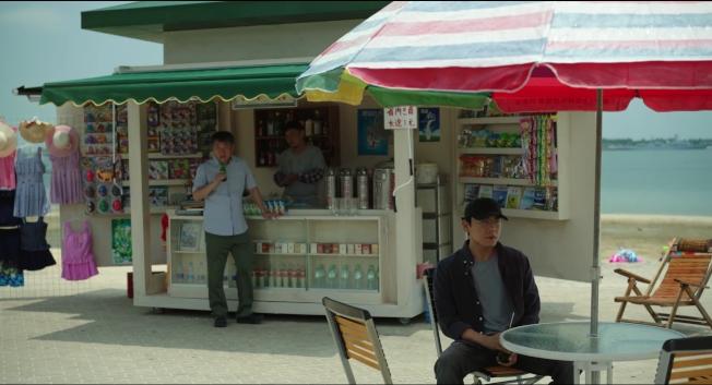 豆瓣上,有觀眾截了這樣一張圖——海邊的小賣鋪陽光暴曬,警察老陳(左)穿著短袖、張東昇不僅全副武裝還戴著帽子。<br />(取材自豆瓣電影)