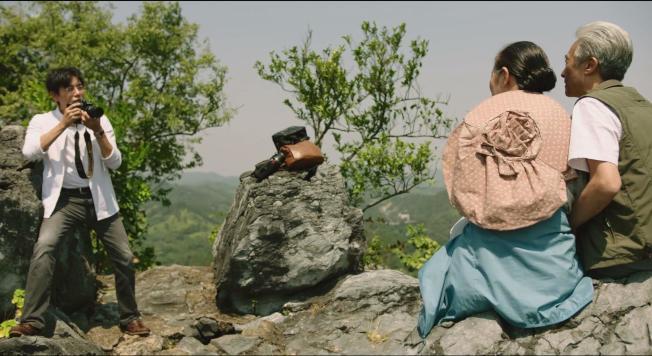 主角張東昇(左)帶著岳父岳母爬山,前一秒還笑瞇瞇地幫二老拍照,後一秒卻猛地把他們推下懸崖。<br />(取材自豆瓣電影)