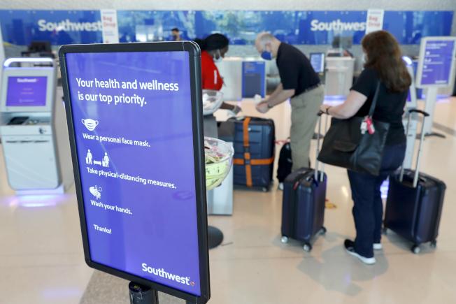 疫情下的機場,多了許多提醒旅客防護的措施。圖為德州達拉斯機場。(美聯社)