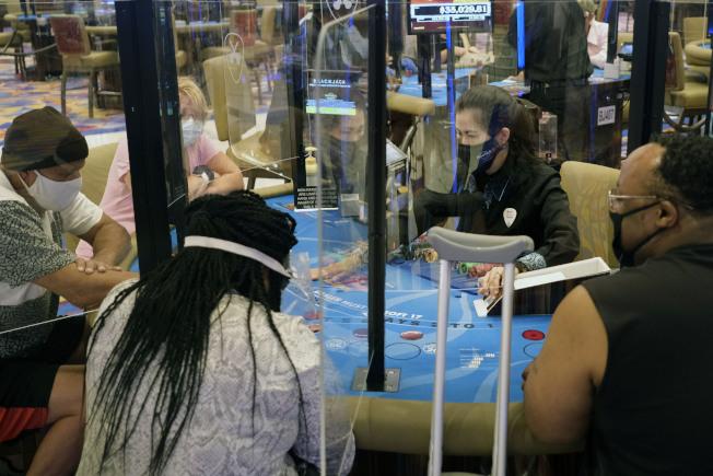 新澤西州大西洋城賭場業者暫停營業長達108天,2日終於重新開放,但賭客必須戴口罩,牌桌則設透明板隔開賭客。(美聯社)