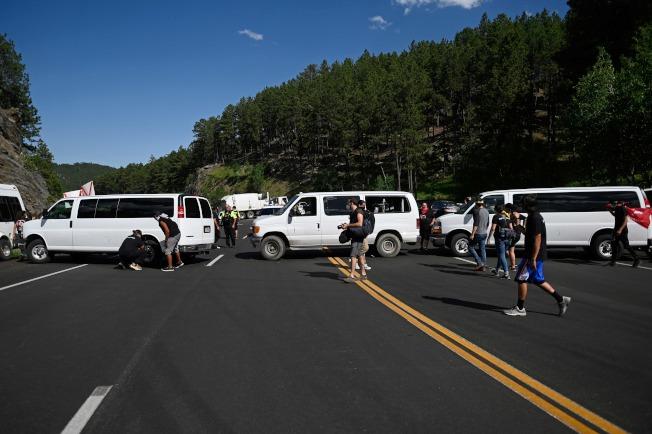 川普總統3日前往南達科他州的總統山國家紀念公園,參加美國國慶煙火施放並發表演說。圖為當地部落的居民,以車輛擋住前往總統山的道路,並卸下輪胎。(Getty Images)