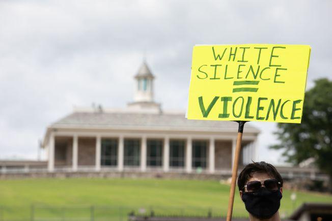 統計指出參加「黑人命也是命」示威活動者中,白人及高收入的群體占最大比例。圖為上月16日抗議者舉牌「白人沉默就等於暴力」的標語站在紀念堂前。(美聯社)