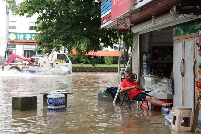 圖為浙江衢州6月30日因大雨導致路面積水,不過當地一名男子仍淡定地在自家雜貨店門口打盹。(路透)