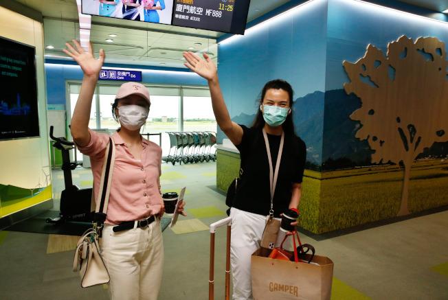 東南衛視駐點記者被要求限期離境,兩名記者艾珂竹(右)及盧嬙(左)3日上午搭機離台,向友人揮手道別。(記者鄭超文/攝影)