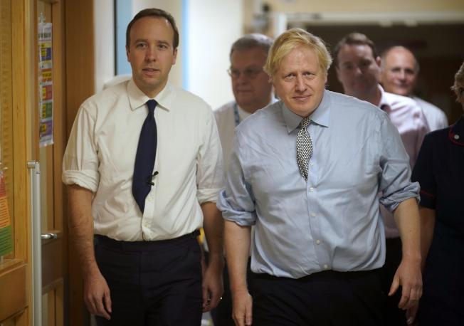 英國首相強生(右)和衛生大臣韓考克(左)2019年一同參訪一家醫院時的檔案照。 美聯社