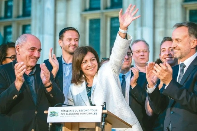 成功連任法國巴黎市長的伊達戈(中),誓言要將汽車趕出首善之都的市中心。(新華社)