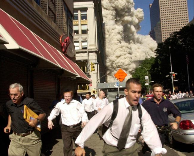 2001年「九一一」當天,紐約世貿中心南座坍塌時,和群眾逃離現場的庫珀(左一),19年後喪命於新冠病毒。(美聯社)