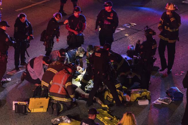 事故發生後,警察及醫護人員在現場救治傷者。(美聯社)