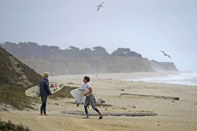 周六國慶日,中半島半月灣有人滑浪,但被警方勸喻離開。國慶周末,聖馬刁縣的海灘都關閉。(美聯社)