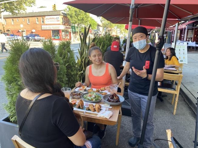 貝爾大道的一鼎鍋在疫情期間被迫關閉兩個月,終在4日迎來了戶外餐廳計畫,可以面對面服務顧客,圖 大廚金敬雯照護顧客。(記者牟蘭/攝影)