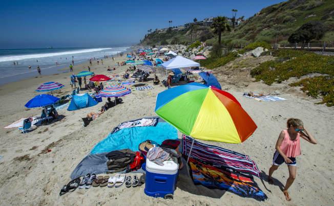 因疫情之故,國慶日南加大部分海灘都關閉,橙縣聖克里門海灘是少數開放的海灘,可以看出遮陽傘之間大多儘量維持六呎的距離。(美聯社)